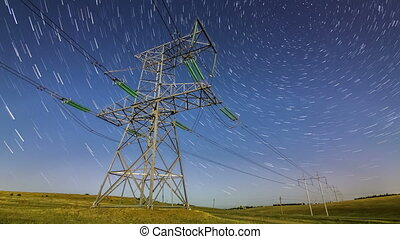 Electric high voltage pylon at night timelapse with rotating starry sky on a background
