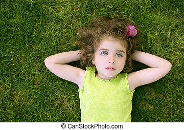 Beautiful little toddler girl happy lying on grass -...