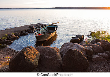 skiff lit on the side by sunset - Lake Skagern a serene...