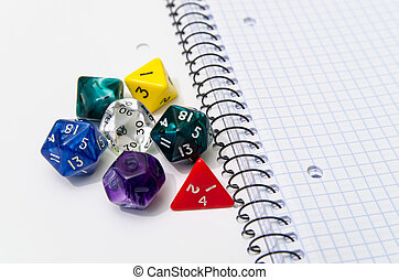 role playing dices lying on exercise book - stock photo