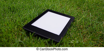 ebook reader lying on wet grass - stock photo