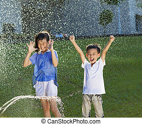 excited kids has fun playing in water fountain