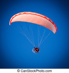 Paraglider - A Paraglider flies in the blue sky