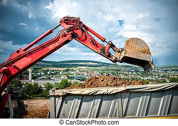 close-up of industrial excavator loading a dumper truck with...