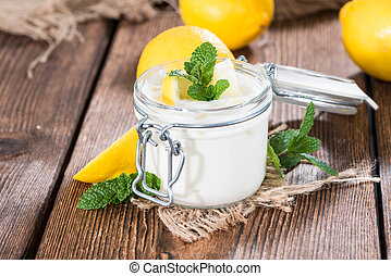 Fresh made Lemon Yoghurt decorated with fresh Mint on wooden...