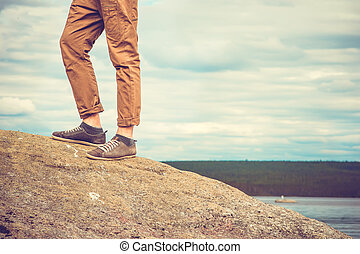 Feet man standing on rocky mountain outdoor Travel Lifestyle vacations concept with sky clouds on background retro colors
