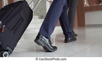 Hotel Lobby - Low angled tracking shot of male feet with...