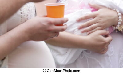 Celebrating childbirth - Group of people clink plastic cups