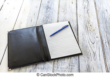 black leather wrapper with a block and blue pen on a rustic...