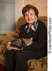 An elderly woman (80 years) with cat in her house.