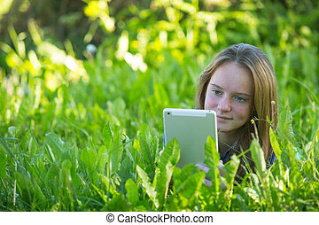 Teen girl with a tablet PC lying in the grass on park.