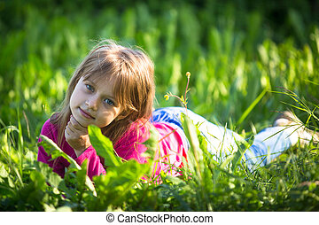 Portrait of little girl in the grass outdoors