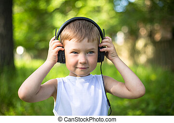 Funny little boy with headphones outdoors.