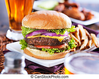 hamburger with fries and beer shot in panorama style with...