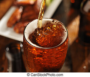 pouring beer into glass with bbq chicken wings in background...
