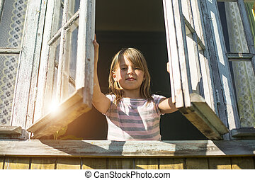 Beautiful little girl looks out the window rural house