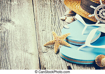 Summer holiday setting with flip flops and straw hat on old...