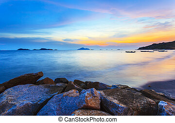 Sunset along the coast with sea stones background