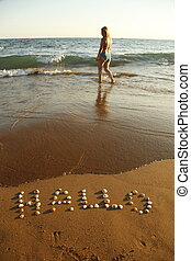 welcome - A woman on the beach with greetings in sand