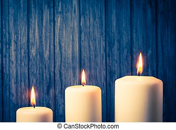 three white candles on warm atmosphere and old wooden...