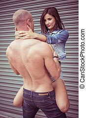 Shirtless man carrying female model - Muscular shirtless man...