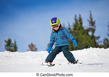 Small boy in ski mask and helmet learns skiing down the hill...