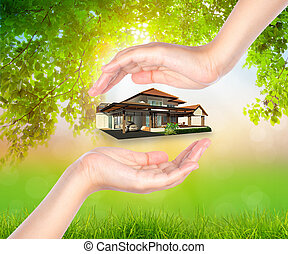 House on woman hand over Green leaf  background