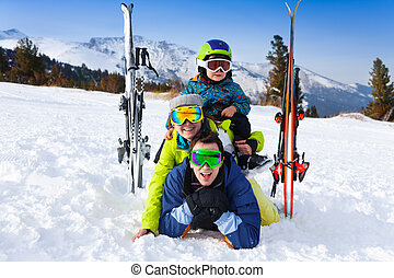 Family in ski masks laying and kid on shoulders - Happy...