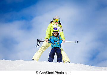 Mother and kid in masks standing with ski polls - Mother and...