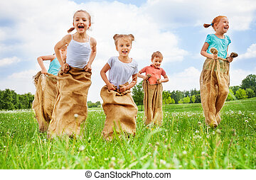 Five kids jump in sacks on a dandelion meadow on summer hot...