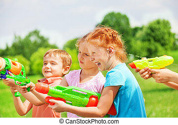 Funny kids playing with water guns