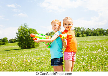 Two wonderful girls play with water guns