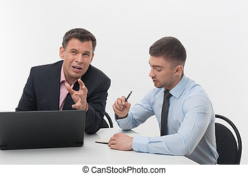 Senior and junior business people discuss something sitting at d