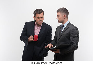 Senior and junior business people discuss something during...