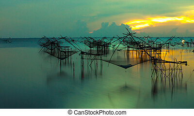 Silhouette of traditional fishing method using a bamboo square d