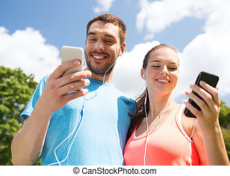 two smiling people with smartphones outdoors - fitness,...