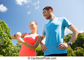 smiling people with heart rate watches outdoors - fitness,...