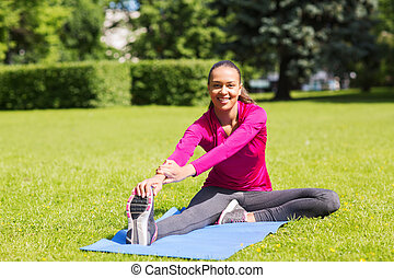 smiling woman stretching leg on mat outdoors - fitness,...