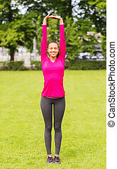 smiling black woman stretching leg outdoors - fitness,...