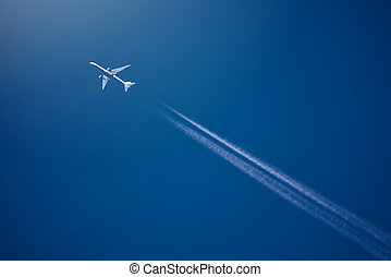 Airliner at high altitude with white condesation trails, on...