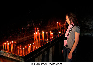 Tourist standing by the candles in Ostrog Monastery,...