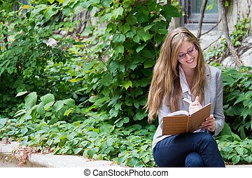 Smiling woman writes in her journal - Beautiful girl writing...