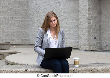Woman frowns while working on laptop - Girl frowning while...