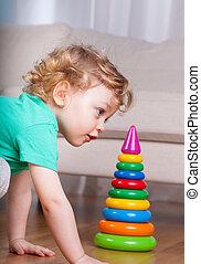 Little boy building plastic tower
