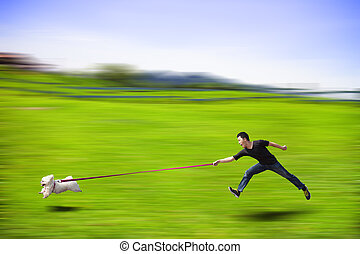 disobedient dog running fast and dragging a man by the leash