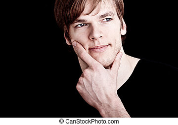 young man thinking in front of black background