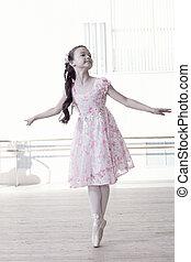 Graceful little girl dancing in ballet studio