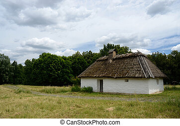 Antique white clay house with hay roof in Pirogovo park,...