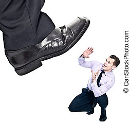 Businessman's foot stepping on tiny businessman - unequal...
