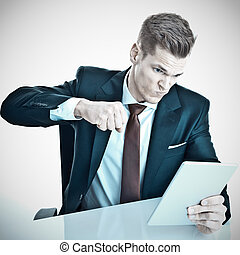 Angry young businessman punching his tablet pc with his fist...